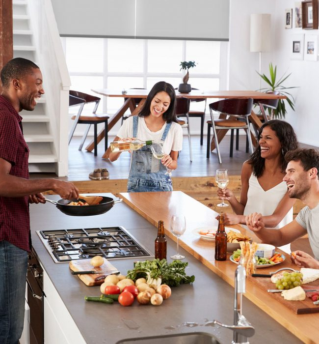 Group of people cooking and eating in front of a set of 18004Blinds blinds