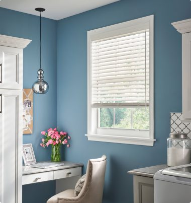 Corner of a light room with a small window with white blinds drawn but open