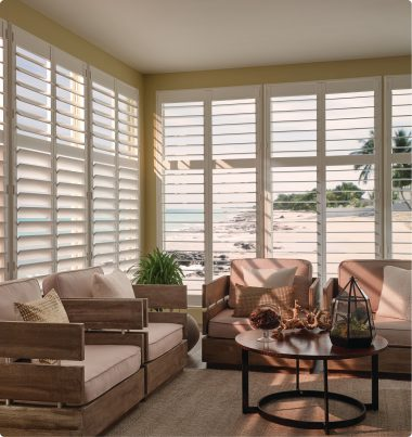 Sitting room with large windows with open shutters. A beach is visible through the shutters.