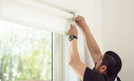 Person affixing controls to a newly-installed set of blinds