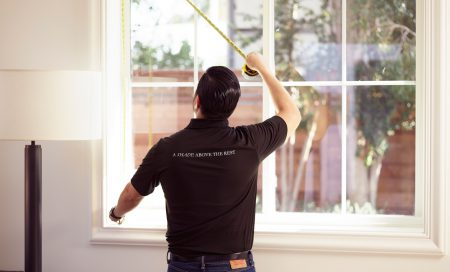 Person measuring a window using a tape measure, with 'A shade above the rest' across the back of their t-shirt