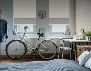 Bedroom with stylish furniture, a white bicycle, and large windows with white blinds