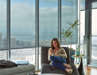 Person relaxing in front of floor to ceiling penthouse windows, with partially drawn roller blinds